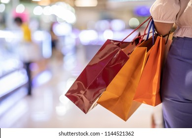 Close up Woman holding shopping bags in her hand walking in shopping mall,Shopping Concept