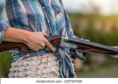 Close up of woman holding a shotgun outside