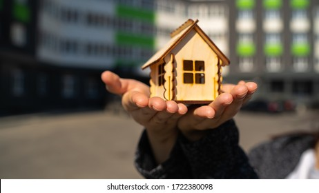 Close up of woman holding small wooden house in hands on background of built house. Concept of purchasing new apartment.