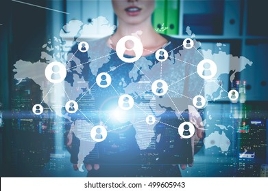 Close up of woman holding tablet computer and standing in office. Sketch of network and world map are in the foreground. Toned image. Double exposure. Elements of this image furnished by NASA