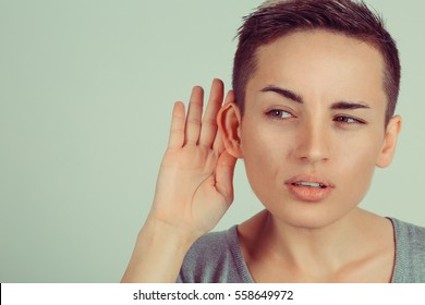 Close up Woman holds her hand near ear and listens carefully isolated on gray wall background. Human emotion body language facial face expression