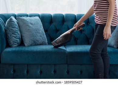 Close up of A woman housewife vacuuming furniture in a house with a hand-held portable vacuum cleaner