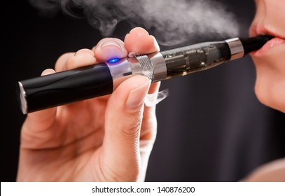 Close up of a woman inhaling from an electronic cigarette
