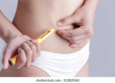 close up of woman inject drugs to prepare for IVF treatment isolated on gray background, model is a asian beauty