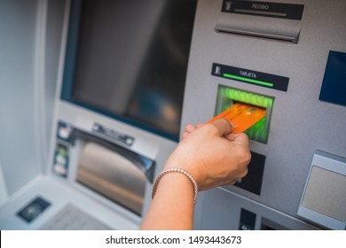 Close up of woman inserting credit card and withdrawing money form cash machine.