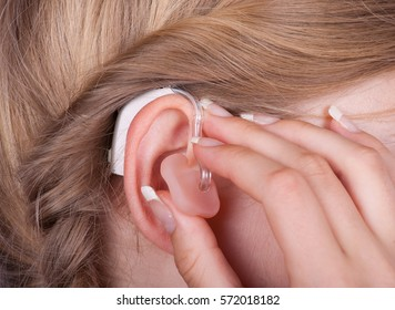 Close up of Woman inserting her hearing aid into ear