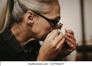 Close up of woman jeweler examining diamond through loupe at workshop. close-up Senior female jeweler looking at diamond through magnifying loupe.