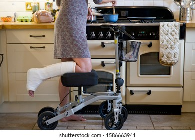 Close Up Of Woman With Leg In Plaster Cast At Home Using Mobility Aid Whilst Cooking Meal