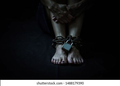 Close up of woman legs bondage with old rusty metal chain and pad lock in the dark room, Conceptual image sex abuse and Slave trade prevention concept with copy space.