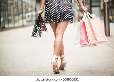 Close up of a woman legs and many shopping bags after shopping. Rear view.