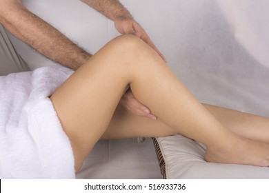 Close up of a woman legs receiving a massage from a man on white background
