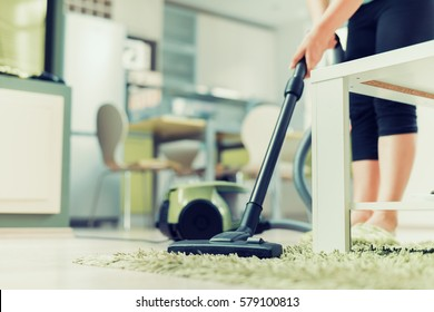 Close up of woman with legs vacuum cleaner cleaning carpet at home.