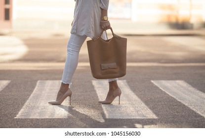 close up of woman legs walking on crosswalk. The woman is wearing shoes on high heels. Handbag in woman hand.