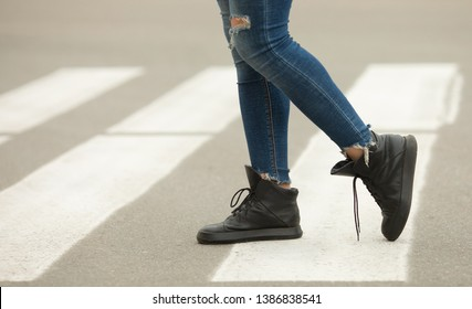 close up of woman legs walking on crosswalk.