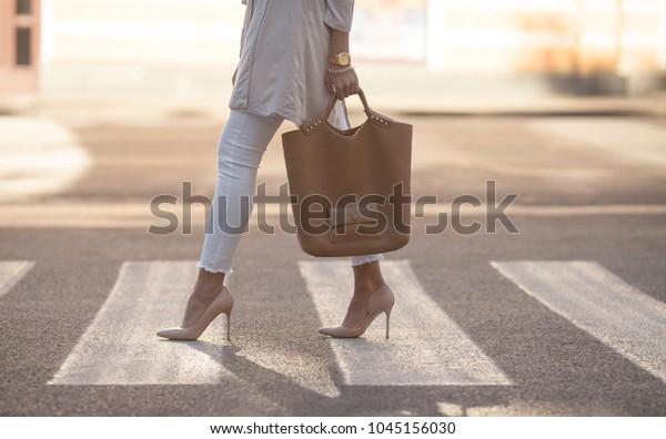 横断歩道を歩く女性の脚の接写。その女性はハイヒールの上に靴を履いている。女手に手袋。