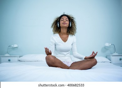 Close up of woman listening to music on head phones while meditating on bed in bedroom