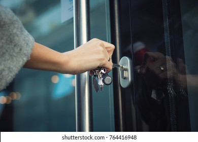 Close up of woman locking entrance door with a key. Person using key and unlocking apartment door.