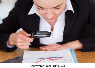 Close up of a woman looking at a chart with a magnifying glass in her office