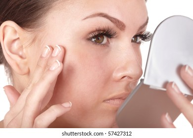 Close up of woman  looking into mirror. Isolated.