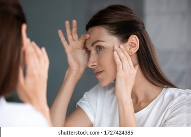 Close up of woman looking in mirror check face after mask cream beauty treatment feels satisfied admire reflection, laser skin resurfacing, glycolic acid peel, anti-ageing skincare procedures concept