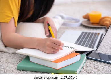 Close up woman lying on carpet and writing on notebook and learning on laptop  at home,work at home concept