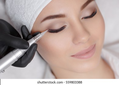 Close up of woman lying on couch at beauty salon with closed eyes and enjoying when cosmetologist making eyeliner permanent make up. Professional wearing black gloves and holding speciality tool.