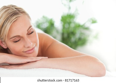 Close up of a woman lying on a lounger eyes closed in a wellness center