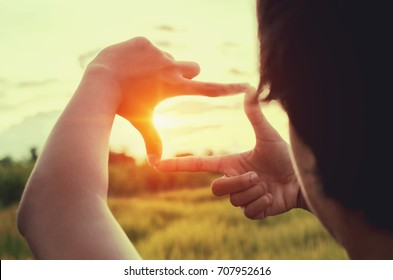 close up woman make hand framing gesture distant with sunset