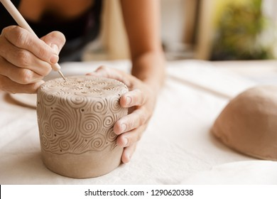 Close up of a woman making ceramic and pottery tableware at the workshop, working with clay