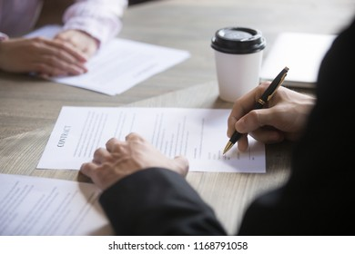 Close up of woman and man hands on the table, the man signs the contract. Lease agreement, successful deal, buy sell real estate concept