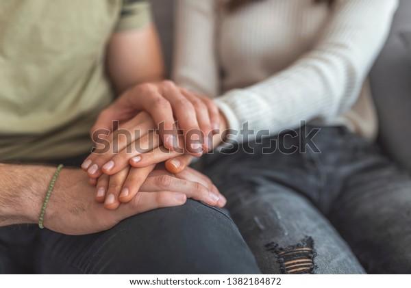 Cierra a la mujer y al hombre enamorado sentados en el sillón, dos personas cogidas de la mano. Signo de símbolo sentimientos sinceros, compasión, ser querido, decir perdón. Persona confiable, amigo de confianza, concepto de verdadera amistad