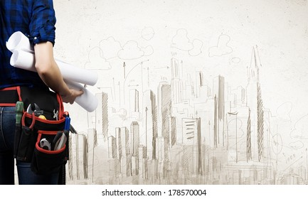Close up of woman mechanic with project in hand against city background