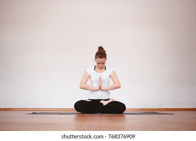 Close up woman meditates while practicing yoga in training hall or home.