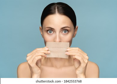 Close up of woman with natural face makeup, holding facial oil blotting paper, hides her lips, looking at camera over blue background. Oil absorbing tissue, shine control, skin care. Beauty product.