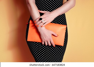 Close up woman with orange bag in hand. Summer outfit and accessories