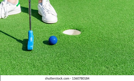 Close up of a woman playing mini golf, with the club about to to hit a ball during a game.