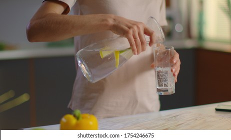 Close up of woman pouring fresh water into glass from jug at home. Attractive girl drinking water on domestic kitchen. Young woman holding glass of water with lemon on kitchen in slow motion