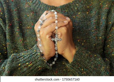 Close up of a woman with prayer hands folded to the chest holding a Rosary beads. Building deeper relationship with through praying The Rosary everyday concept.