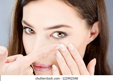 Close up of a woman putting contact lens in her eye