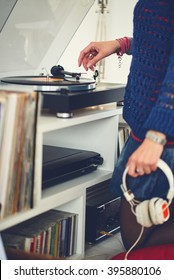 Close up of a woman putting needle on vinyl record