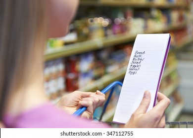 Close Up Of Woman Reading Shopping List In Supermarket