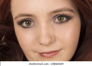 A close up of a woman with red hair, looking.