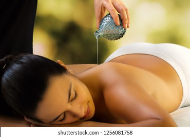 Close up of woman relaxing in low light spa.Therapist pouring massage oil on back.