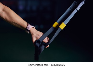 Close up of woman s hand holding TRX strap over dark background.