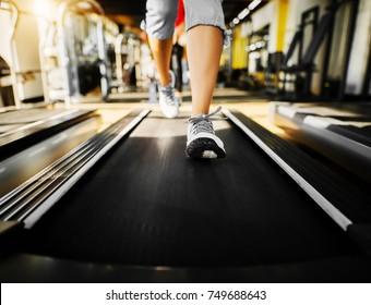 Close up of woman shape legs while running on the treadmill in the sunny gym.