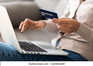 Close up woman shopping, paying by credit card, buying goods or ordering online, using laptop, login internet bank service, typing on keyboard, checking balance, sitting on sofa at home