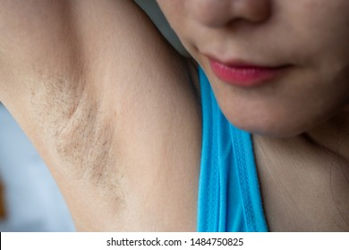 Close up of woman showing her unshaved armpit. Unshaven women often meet other criteria for traditional feminine beauty.