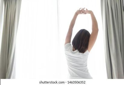 Close up woman sitting on the bed and stretching after waking up for relax in the morning with over light background