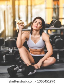 Close up of a woman is sitting on a mat in the gym and holding a banana while workout break in a fitness gym. Lifestyle and health.