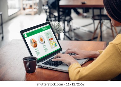 Close up woman sitting and orde food online on laptop computer in add to cart function webpage at coffee shop,Digital marketing concept.digital lifestyle living